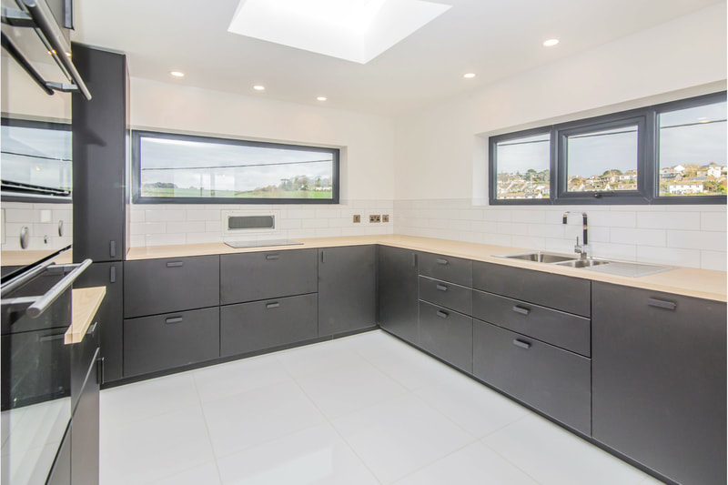 Black and wood kitchen with white porcelain floor